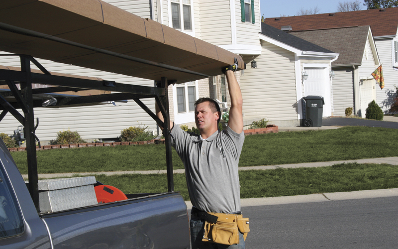 Affordable Garage Door Service Technician Unloading New Door From His Truck