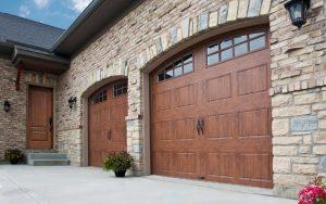 Beautiful Clopay Wooden Garage Doors on a brick home