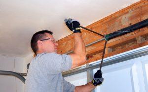 Garage Door Repair Technician repairing a broken garage door spring