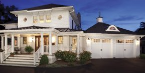 house with attached garage at night concept for skilled garage door maintenance company in Lowell